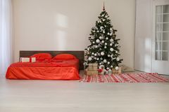 Chambre à coucher avec le lit de décoration d'arbre de nouvelle année de Noël Photographie stock libre de droits