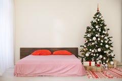 Chambre à coucher avec le lit de décoration d'arbre de nouvelle année de Noël Photo libre de droits