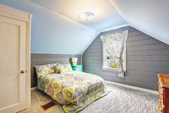 Chambre à coucher avec le plafond voûté et les murs lambrissés par planche Image stock