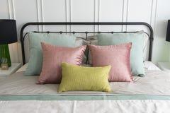 Chambre à coucher avec le rose en pastel et les oreillers verts d'accents photos stock