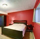 Chambre à coucher avec les murs rouges Meubles noirs de couleur et couverture beige Photo stock