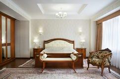 Chambre à coucher classique avec un grand double lit, tables de chevet, chaises image libre de droits
