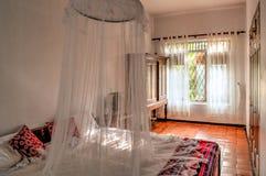 Chambre à coucher coloniale de style avec la moustiquaire Photo stock