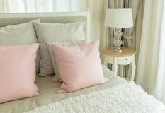 Chambre à coucher confortable avec les oreillers et la lampe de lecture roses sur des lits Photo libre de droits