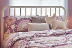 Chambre à coucher confortable avec les oreillers gris et roses sur le lit Photo stock