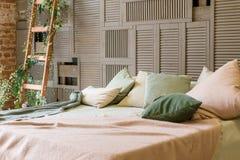 Chambre à coucher confortable de couleurs en pastel avec le mur en bois brun et les meubles en bois simples dans le style minimal image stock