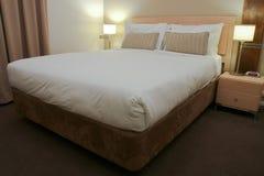 Chambre à coucher d'hôtel avec des lampes de bâti et de côté Photographie stock libre de droits