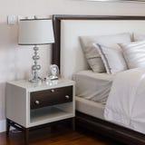 Chambre à coucher de luxe avec la lampe et l'horloge classiques blanches sur la table Image libre de droits