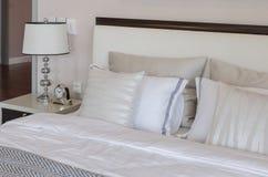 Chambre à coucher de luxe avec la lampe et l'horloge classiques blanches sur la table Photos libres de droits