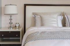 Chambre à coucher de luxe avec la lampe et l'horloge classiques blanches sur la table Photo libre de droits