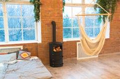 Chambre à coucher de style de grenier avec le mur de briques avec l'hamac et l'appareil de chauffage en bois, intérieur de concep photographie stock