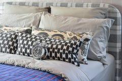 Chambre à coucher moderne avec les oreillers noirs et blancs sur le lit et le réveil décoratif photos stock