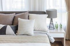 Chambre à coucher moderne de style avec des oreillers sur le lit et la lampe grise moderne dessus Image stock
