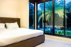 Chambre à coucher principale moderne avec les vitraux larges pendant la soirée ou le matin Photographie stock libre de droits
