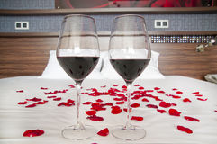 Chambre à coucher romantique - verres de vin rouge et de pétales de rose sur un lit Photographie stock