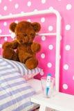 Chambre à coucher rose avec l'ours et le thermomètre de jouet Photos libres de droits