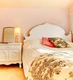 Chambre à coucher rose avec le bâti et le nightstand blancs photographie stock libre de droits