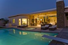 Chambre avec des chaises longues sur le patio par la piscine au crépuscule Image stock