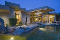 Chambre avec la piscine dans l'arrière-cour au crépuscule Photo stock