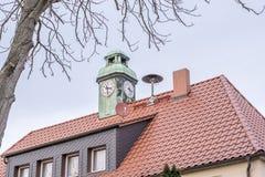 Chambre avec la tour d'horloge et la sirène du corps de sapeurs-pompiers local sur le toit images libres de droits