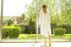 Chambre d'hôtel complètement des faisceaux du soleil de lumière du soleil Début optimiste Femme blonde, habillement à la maison c photo libre de droits