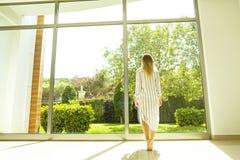 Chambre d'hôtel complètement des faisceaux du soleil de lumière du soleil Début optimiste Femme blonde, habillement à la maison c photos libres de droits