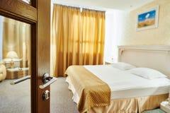 Chambre d'hôtel avec la porte ouverte et la chambre à coucher à l'arrière-plan Photographie stock libre de droits