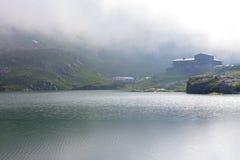 Chambre dans le brouillard sur le rivage d'un lac de montagne images stock