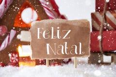 Chambre de pain d'épice avec le traîneau, flocons de neige, Feliz Natal Means Merry Christmas Photographie stock libre de droits