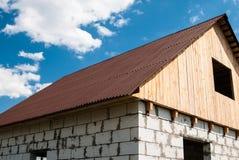 Chambre des blocs avec le toit des tuiles et du grenier en bois sous un b Photographie stock