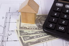 Chambre des blocs et du dollar en bois de devises avec la calculatrice sur le dessin de construction, concept de maison de bâtime Photos libres de droits