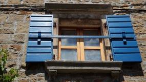 Chambre en pierre avec les volets bleus de fenêtre Images libres de droits
