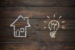Chambre et ampoule dessinées sur les conseils en bois Dessin avec la craie photos stock