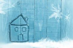 Chambre faite à partir des bâtons secs sur le fond en bois et bleu placements Image de neige et de flaks de neige photographie stock