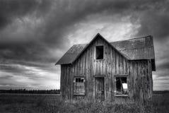 Chambre hantée abandonnée de ferme avec le ciel orageux photographie stock libre de droits