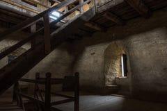 Chambre noire avec la fenêtre de murs en pierre et l'escalier en bois Image libre de droits