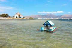 Chambre pour des canards sur l'eau dans le village d'Elafonisos sur le fond de l'église d'Agios Spyridon et du paysage marin pitt Photographie stock libre de droits