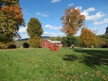 Chambre rouge de ferme sur un champ d'herbe Image libre de droits