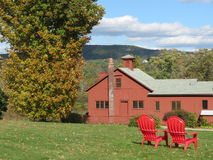 Chambre rouge de ferme sur un champ d'herbe Photographie stock libre de droits
