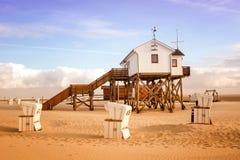 Chambre sur les enjeux en bois sur la plage et les chaises de plage en osier image stock