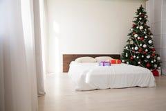 Chambres à coucher de Noël avec la carte postale d'arbre de nouvelle année de cadeaux de lit photographie stock