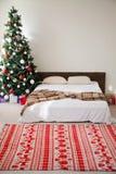 Chambres à coucher de Noël avec la carte postale de nouvelle année de cadeaux d'arbre de lit images stock