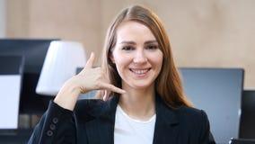 Chame-nos, contacte-nos, gesto pela mulher no escritório foto de stock