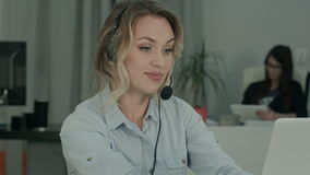 Chame o operador com auriculares usando o portátil na mesa no trabalho vídeos de arquivo