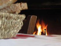 Chaminé ardente com a cesta do pão e da cadeira velha do vintage em uma atmosfera do país Imagens de Stock Royalty Free