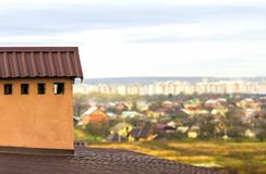 Chaminé em um telhado de uma casa construída nova com vista de uma cidade abaixo imagens de stock