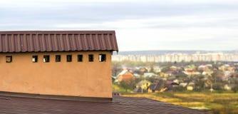 Chaminé em um telhado de uma casa construída nova com vista de uma cidade abaixo fotos de stock
