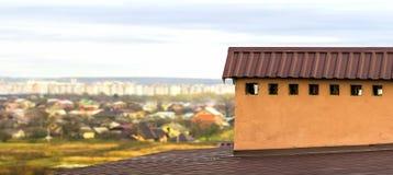 Chaminé em um telhado de uma casa construída nova com vista de uma cidade abaixo imagem de stock