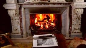 Chaminé, fogo e livro de mármore cinzelados antiguidade na tabela, mulher que lê um livro filme