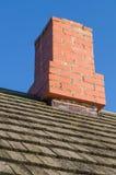 Chaminé Redbrick e telhado de madeira da prancha do vintage Foto de Stock